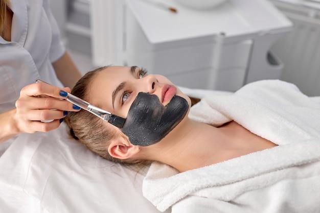 クライアントの顔に顔のマスクを適用する白人の美容師の女性の手