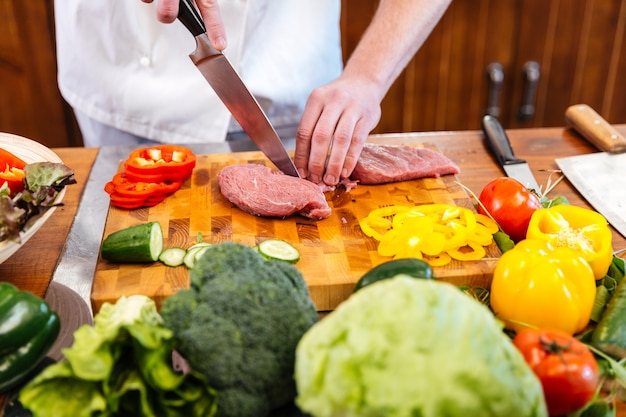 シェフの手がテーブルの上で新鮮な野菜を使って肉を切って調理する