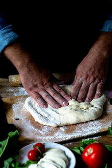 シェフの手イタリア人シェフがピザを調理する男の手がピザ生地を調理するピザが調理する手