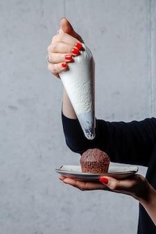 灰色の背景に菓子バッグとカップケーキにクリームを絞るシェフの手。プロのコンペット。デザインのスペースをコピーします。垂直。食品のコンセプト