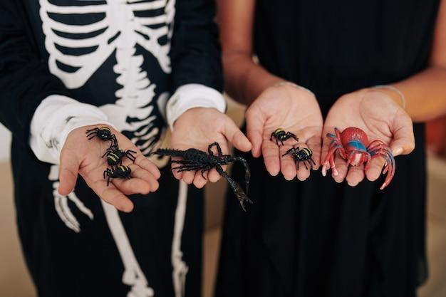 怖いプラスチックのクモと蠍座を示すハロウィーンパーティーで子供たちの手