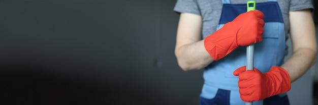 モップハンドルを保持している黄色い手袋のクリーナーの手