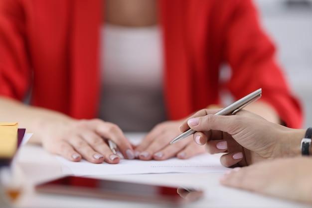 Руки коллег с шариковой ручкой, лежащие на документах крупным планом
