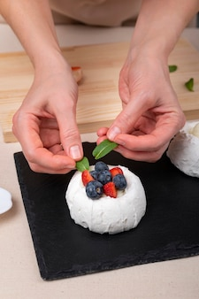 Руки кондитера украшают торт. свежие ягоды, мята и белое безе.