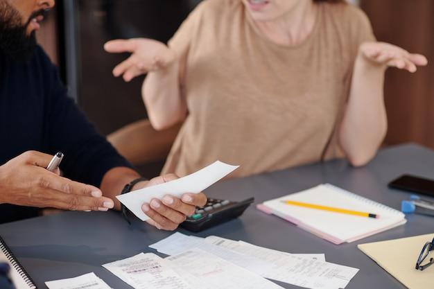 Руки сбитого с толку мужчины показывают квитанцию жене, которая сделала большую покупку и потратила много денег, не поговорив сначала с ним
