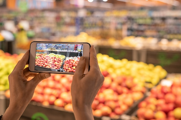 Руки современного покупателя супермаркета, держащего смартфон и фотографирующего дисплей со свежими фруктами и овощами