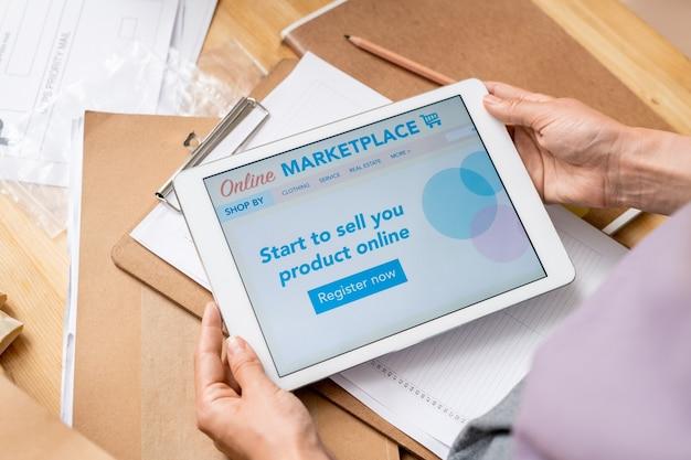 Руки современной женщины-менеджера интернет-магазина с сенсорным экраном, показывающим домашнюю страницу с названием веб-сайта, опциями и кнопкой регистрации
