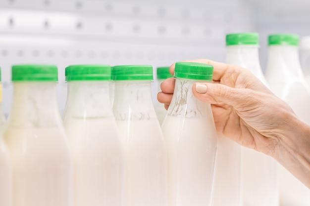 乳製品の棚から緑の蓋付きのケフィアのペットボトルを取っている現代の成熟した女性消費者の手が表示されます