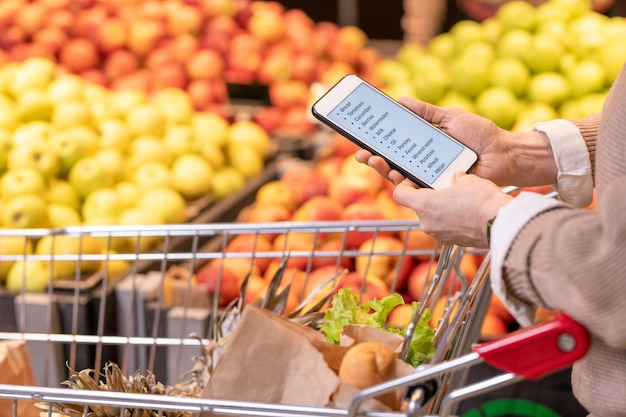 Руки современной зрелой покупательницы со смартфоном над продуктами питания в тележке, просматривающей список покупок
