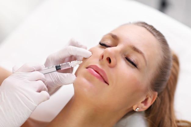 女性の唇にボトックス注射をする美容師の手