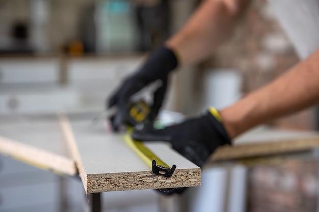 巻尺と鉛筆を使って置かれた木片に印を付ける職人の手。