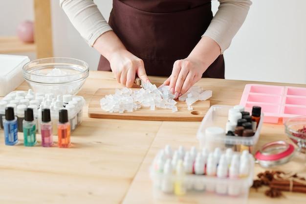 さらなる処理の前に、木製のテーブルでボード上の透明な石鹸の塊を切る職人の手