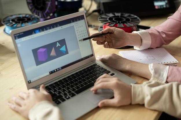 Руки креативных дизайнеров у дисплея ноутбука с эскизом геометрических фигур во время обсуждения или презентации