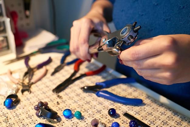 テーブルの上に装飾をしながら、革片の端の1つに小さな金属クリップを固定するハンドツールを持つ創造的な女性の手