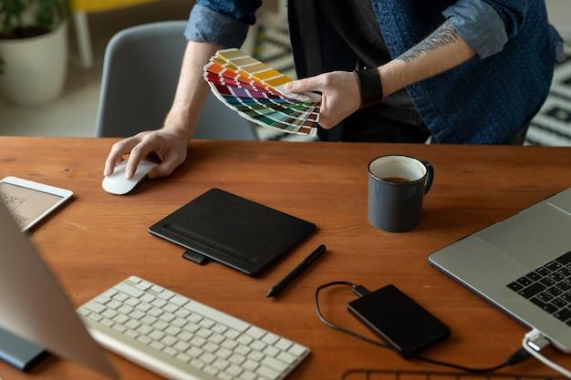 Руки творческого разработчика программного обеспечения или веб-дизайнера с цветовой палитрой склоняются над деревянным столом перед компьютером во время работы