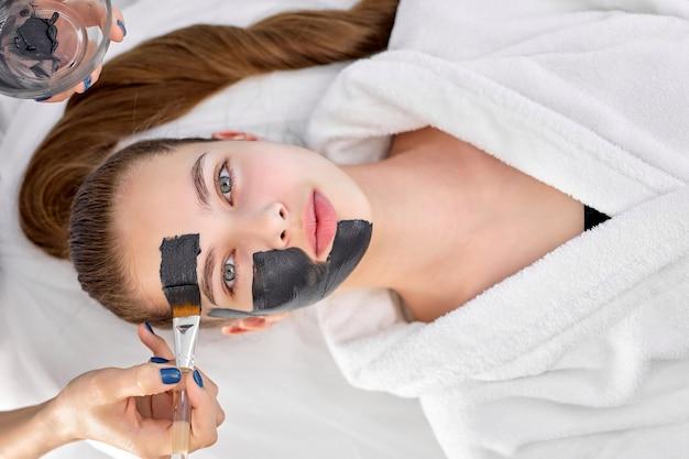 マッサージベッド、上面図の肖像画に横たわっている美しい若い白人女性の顔に顔のマスクを適用するトリミングされた白人の美容師の女性の手。コピースペース。美容、スキンケア、スパのコンセプト