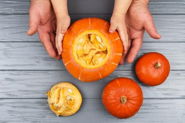 Руки дочери и отца возле тыквы перед резьбой на хэллоуин.