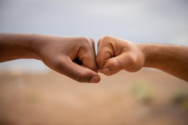 인종 차별에 맞서 싸우는 다른 색의 손. 두 주먹이 만지고, 하나는 흰색 (코카서스 인), 다른 하나는 검은 색 (아프리카)