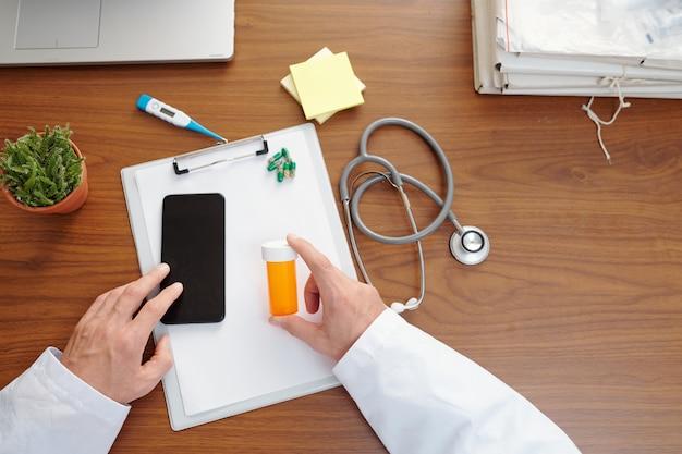患者の処方箋を書くときにスマートフォンをチェックする医師の手、上からの眺め