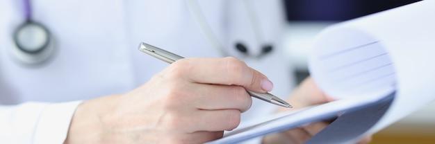 클립 보드를 들고 펜으로 시험 결과를 작성하는 의사의 손에 완료