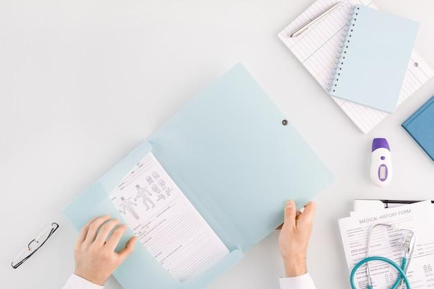 Руки врача открывают папку с медицинским документом, собираясь достать ее, чтобы прочитать, сидя на рабочем месте с другими принадлежностями рядом