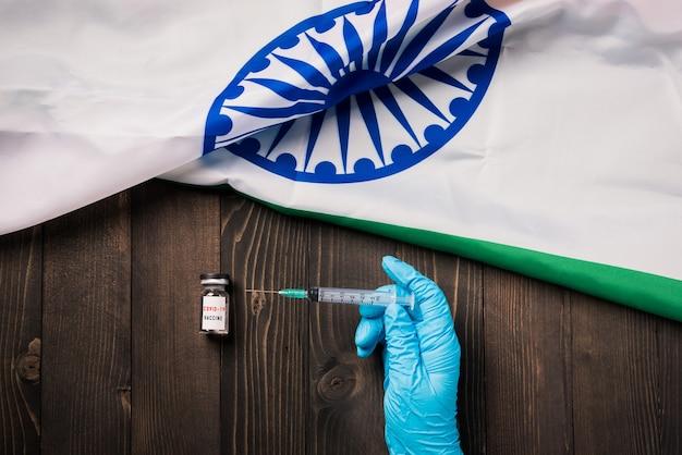 コロナウイルス(covid-19)バイアルワクチンと注射器を保持している手袋を着用した医師の手