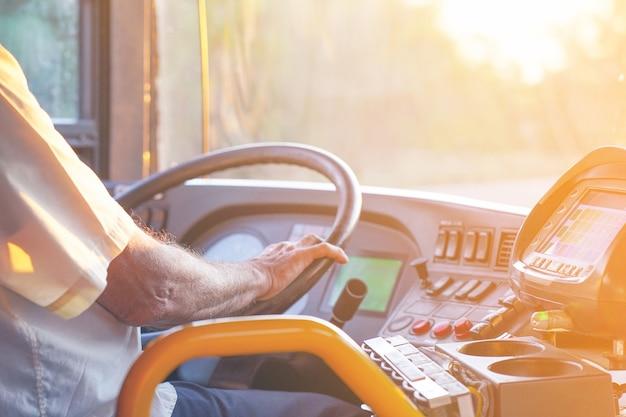 운전하여 현대 버스에서 운전자의 손. 버스 운전사 스티어링 휠 및 운전 승객 버스의 개념. 토닝.