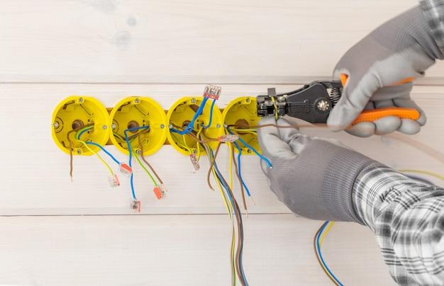 새 목조 주택의 벽에 드라이버로 전기 소켓을 설치하는 전기 기술자의 손