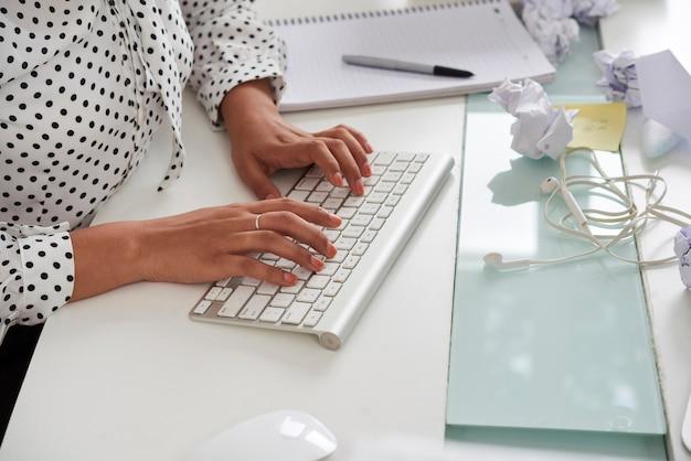 しわくちゃの紙のキーボード片とfrのドキュメントを入力するエレガントな女性起業家の手...