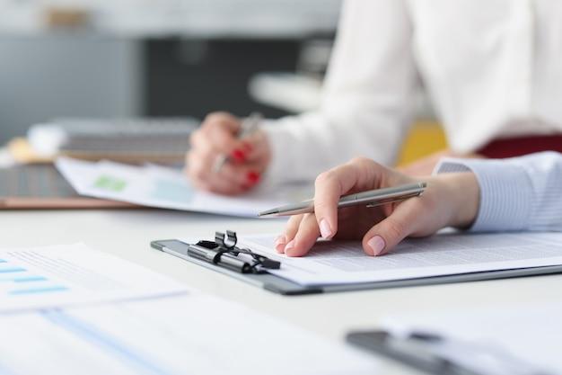 펜과 비즈니스 문서가 있는 작업 테이블에 있는 직원의 손