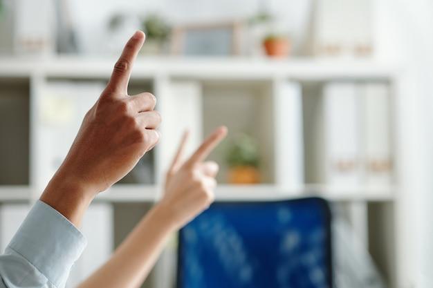 ビジネス会議で質問するために手を上げる従業員の手、前景に焦点を当てる
