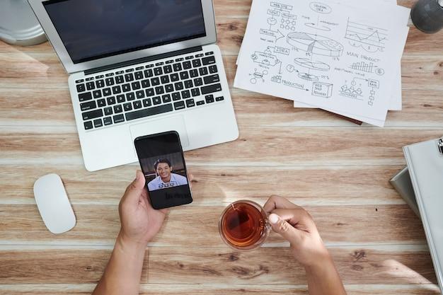 お茶を飲みながら同僚にビデオ通話をして、レポートについて話し合ったり、プロジェクトの作業を計画したりする起業家の手。上から見る