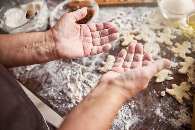 밀가루로 덮인 숙련된 제빵사의 손