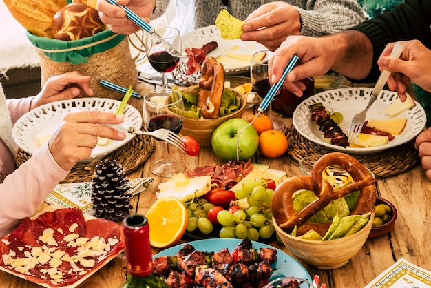 ダイニングテーブルにフォークで食べ物を選ぶ家族の食事の手。スライスした肉、テーブルに置いたパンと新鮮な果物。ボトルとグラスにワインを入れた作りたての調理済み食品と収穫された果物。