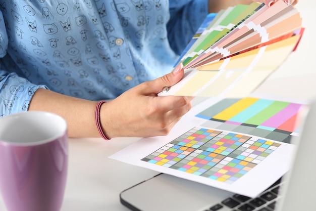 Руки дизайнера женского пола в офисе, работающем с образцами цвета. женщина на рабочем месте, выбирая красочные бумажные диаграммы. творческие люди или рекламная бизнес-концепция