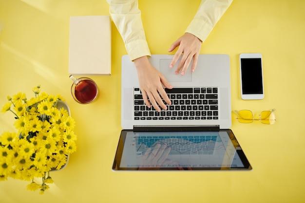 밝은 노란색 테이블에 앉아 노트북에서 작업하고 차를 마시는 여성 기업가의 손