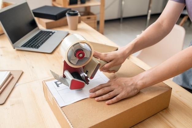 셀로테이프 총 디스펜서가 있는 온라인 상점의 여성 관리자의 손에 그녀의 직장에서 클라이언트의 포장된 주문이 있는 판지 상자를 밀봉
