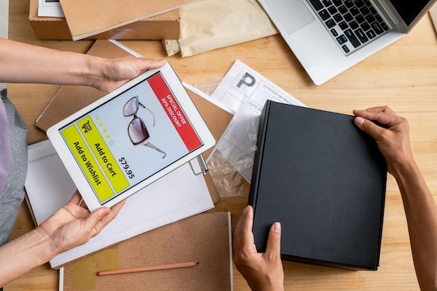 Руки менеджеров интернет-магазина держат планшет с фото солнцезащитных очков на экране и упаковывают черный ящик с заказом клиента
