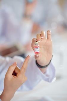 Covid-19に対するワクチンの入った小さなバイアルを見せている女性科学者の手