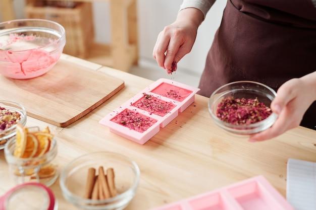Руки женщины обсыпают сухие натертые лепестки цветов на розовые бруски мыла ручной работы в силиконовых формочках во время мастер-класса