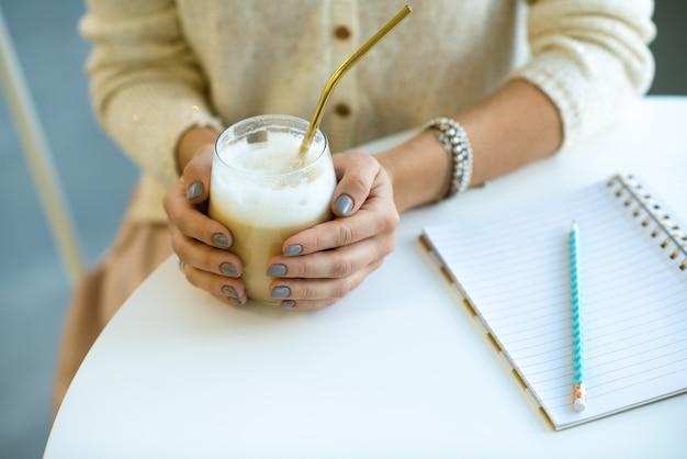 休憩時間にテーブルのそばに座って宿題をしながら、ストローでカプチーノのガラスを保持している女子学生の手