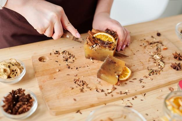 Руки женщины с ножом, режущие большой кусок мыла ручной работы с корицей, анисом и дольками апельсина на деревянной доске