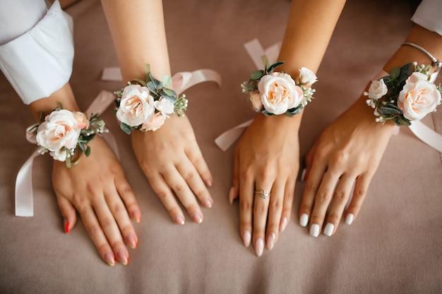 手に結ばれた花を持つ4人の女性の手