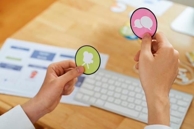 彼が新しいモバイルアプリケーション用に作成したアイコンを選択するフリーランスのグラフィックデザイナーの手