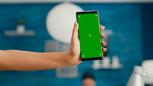 垂直モックアップグリーンスクリーンクロマキースマートフォンを保持しているフリーレンサーの手。オフィスの机の上に座ってソーシャルネットワークを閲覧するために分離された電話を使用してビジネス女性