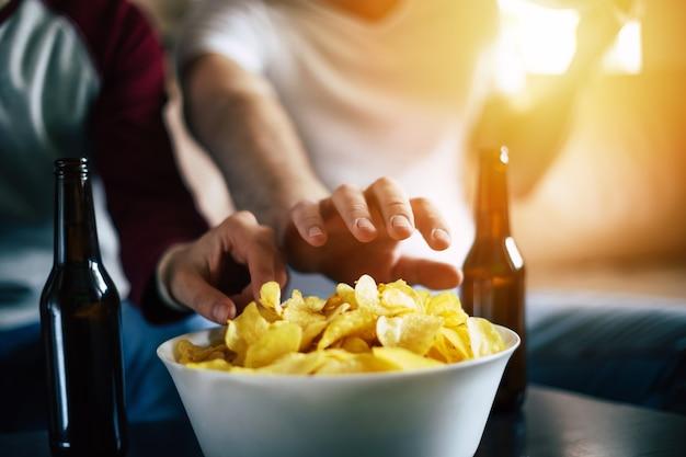 병 맥주와 함께 테이블에 서있는 유리 그릇에서 칩을 먹는 친구의 손.
