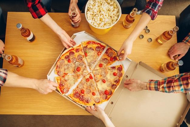テーブル、上面図、ホームパーティーからピザのスライスを取る友人の手。 g