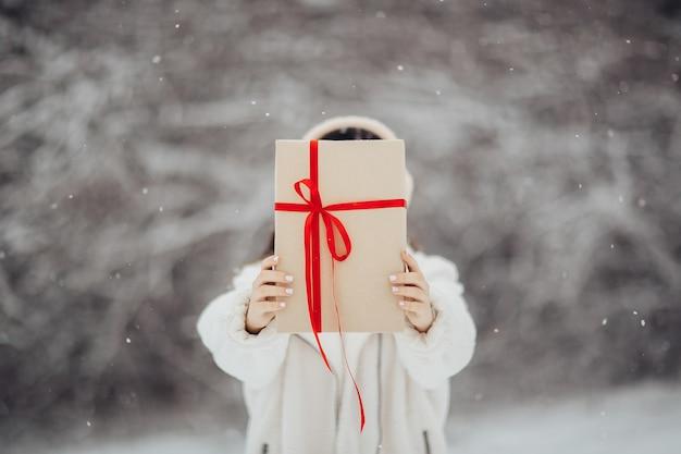 Руки девушки держат подарочную коробку с красной лентой. концепция зимних праздников. день святого валентина.