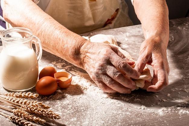 おばあちゃんの手が生地をこねます。 80歳の女性の手練り生地。自家製のベーキング。ペストリーと調理
