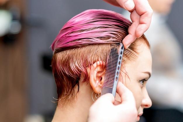 美容師の手がサロンで女性の髪をとかしている、クローズアップ。